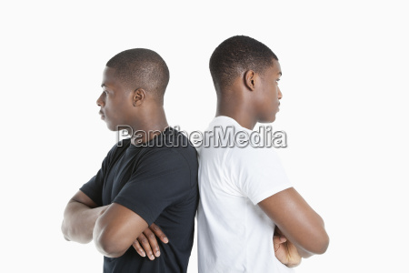 two male friends standing back to