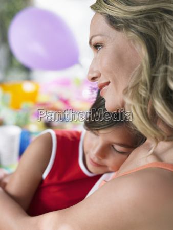 mother with sleeping daughter at birthday