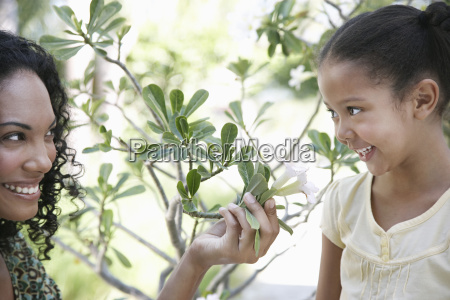 mother showing flower plant to daughter