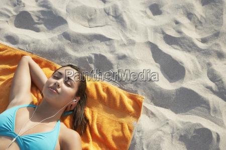 teenage girl listening music while lying