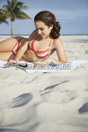 teenage girl reading magazine on beach