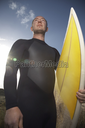 man in wetsuit carrying surfboard on