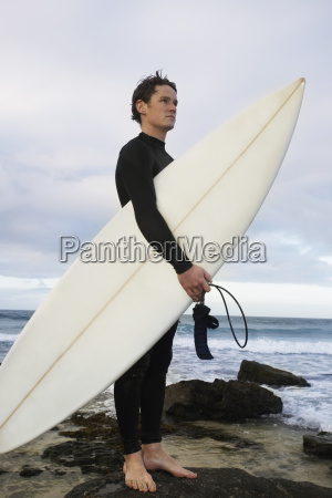 man with surfboard standing on rock