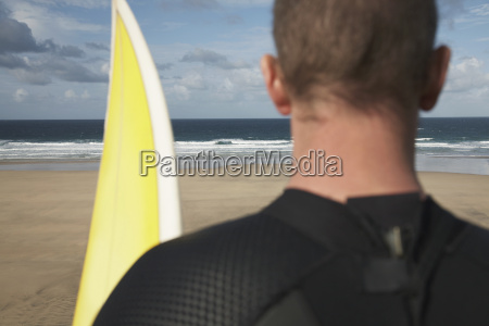 surfer with surfboard on beach looking