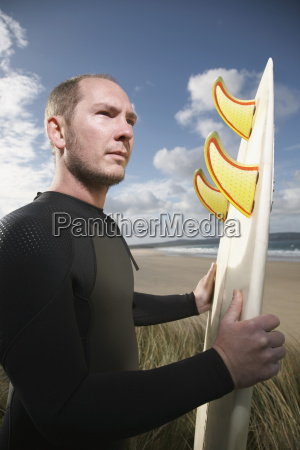 surfer carrying surfboard on beach looking