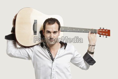 portrait of young man carrying guitar