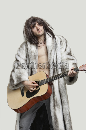 young man in fur coat playing