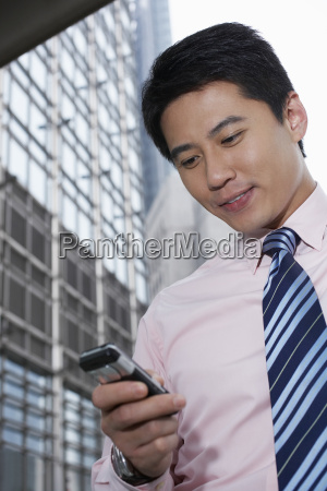businessman using cell phone outside office