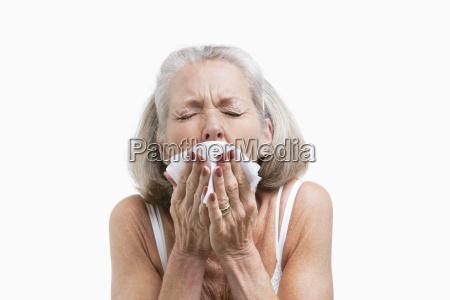 seniorenfrau niest vor weissem hintergrund in
