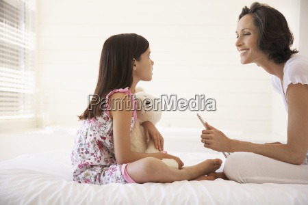 happy mother with daughter on bed