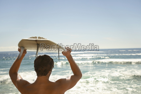 man carrying surfboard above head by