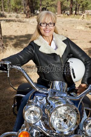 aeltere frau sitzt auf motorrad mit