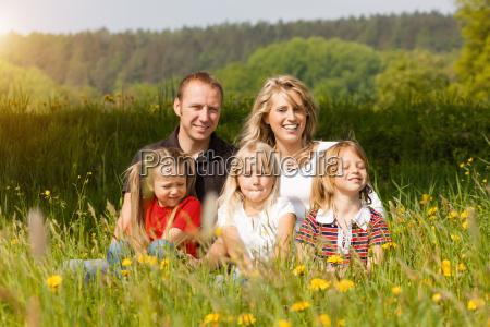 glueckliche familie im sommer auf wiese