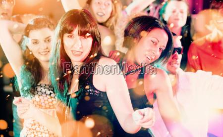 frauen und maenner tanzen im club