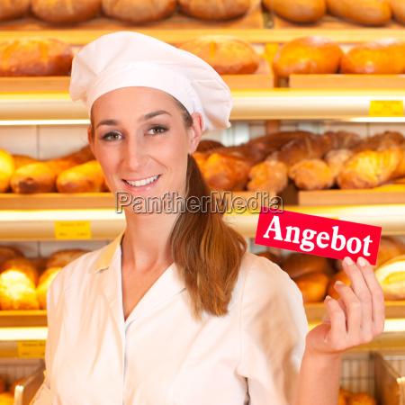 female baker selling bread in bakery