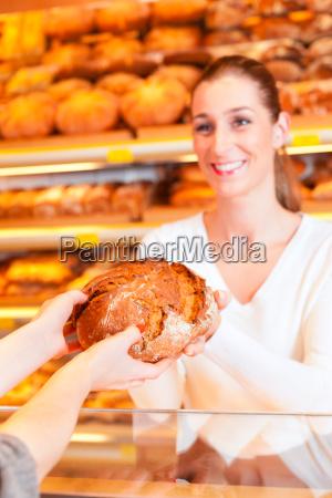 verkaeuferin mit weiblichen kunden in baeckerei