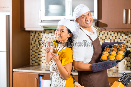 asian couple baking muffins in home