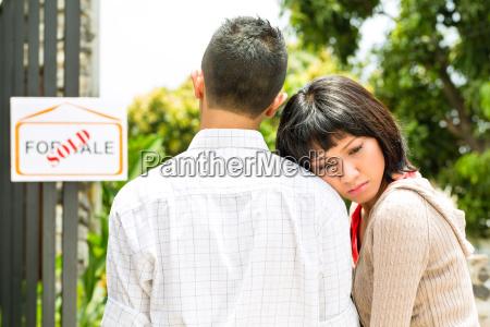 enttaeuschtes asiatisches paar vor einem haus