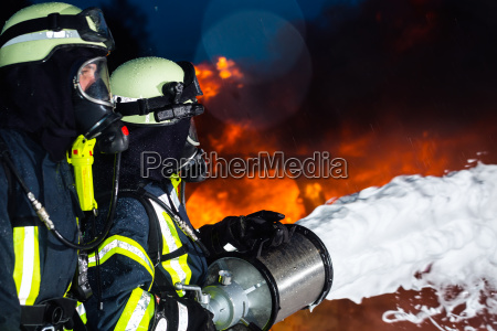 feuerwehrmann feuerwehrleutedie eine grosse flamme