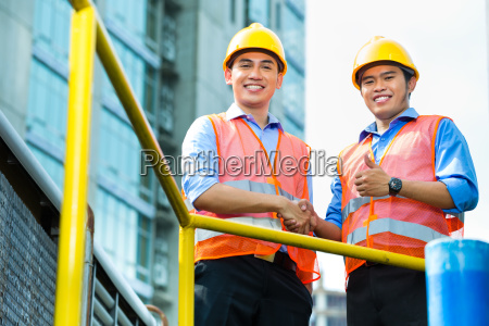 asian indonesian construction workers on building