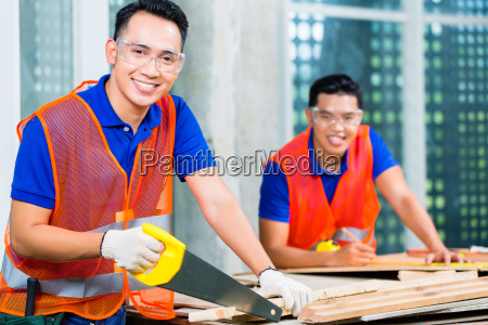 builder sawing a wood board of