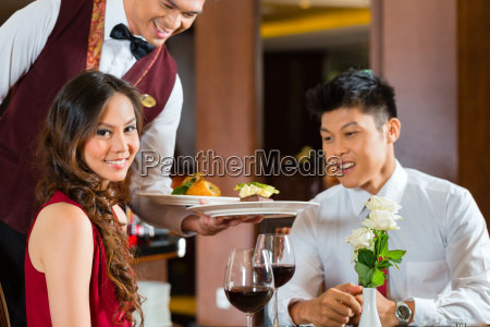 chinese waiter serving dinner in elegant