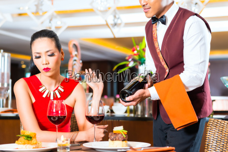 waiter showing bottle of wine in