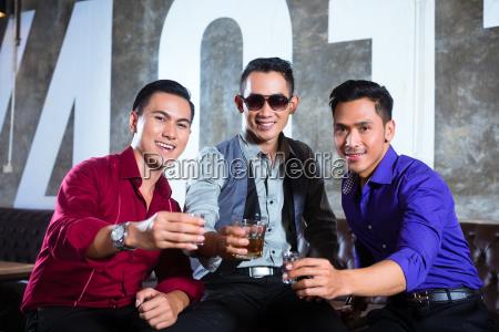 asiatische freunde trinken schuesse im nachtclub