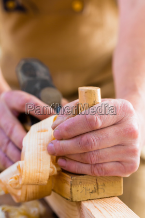 carpenter with wood planer and workpiece