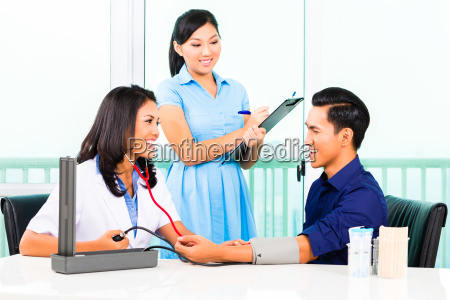 asian doctor check up blood pressure