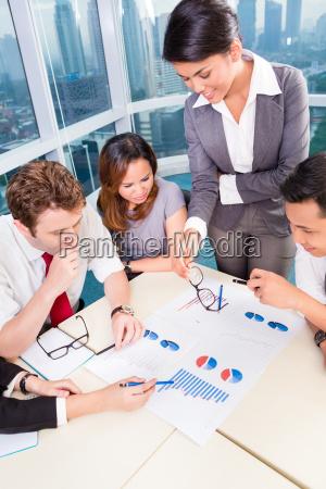 asian business team diskutiert diagramme