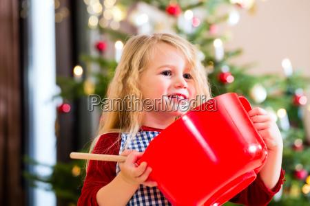 maedchenbackenplaetzchen vor weihnachtsbaum