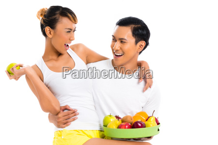 asian couple eating fruit and living