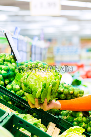 woman buying vegetables in supermarket