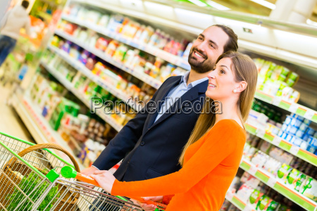 couple with cart grocery shopping in