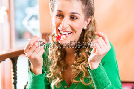 woman eating cake at pastry shop