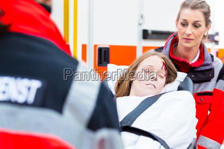 ambulanz hilft verletzten frau auf trage