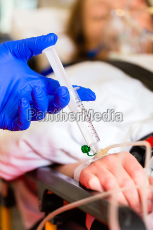 paramedic giving infusion in ambulance