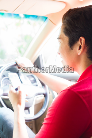 asian man texting message while driving