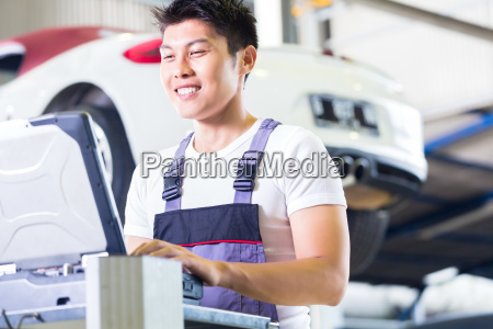 car mechanic with diagnosis tool in