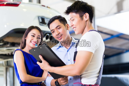 car mechanic and asian customer couple