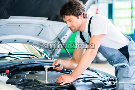 mechanic with diagnostic tool in car