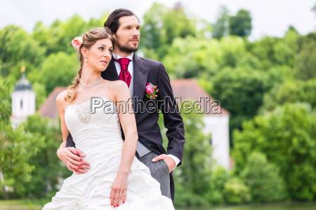 bridal pair in park groom holding