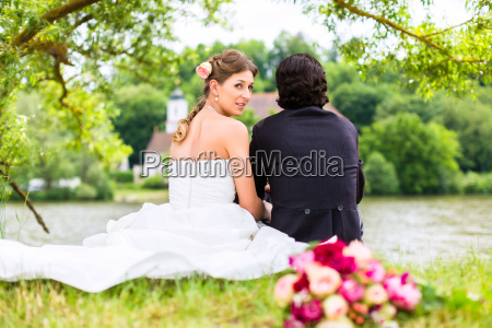 bridal pair with bouquet on meadow
