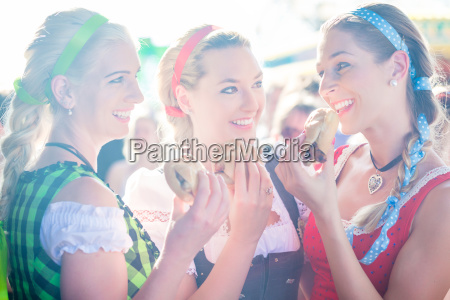friends eating grilled sausage at oktoberfest