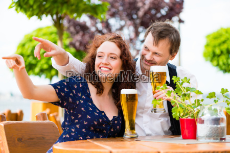 man and woman sitting in beer