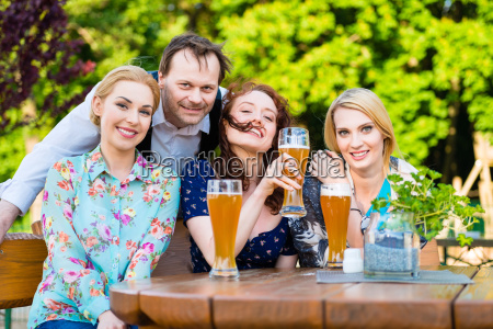 friends sitting in beer garden restaurant