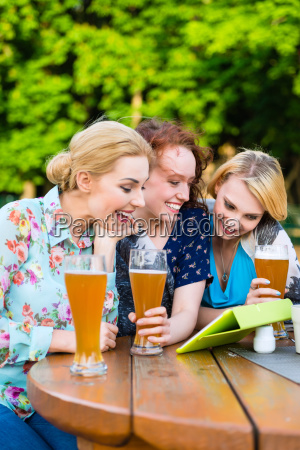 woman showing friends touch pad in
