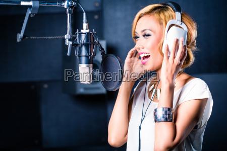 asiatischer saenger der lied im aufnahmestudio