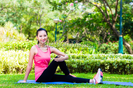 asian chinese woman stretching muscles for